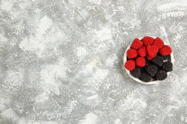 上面図新鮮なベリーは白い表面のプレートの内側に甘いキャンディーを構成しますベリーキャンディーシュガースイートケーキパイクッキー 無料写真