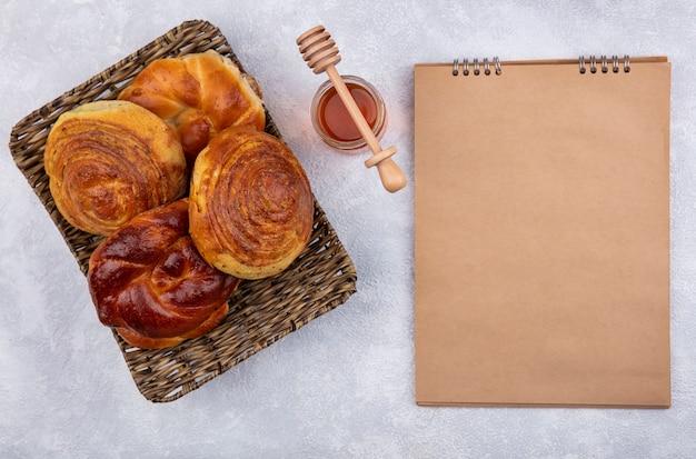 Vista dall'alto di panini freschi sul vassoio di vimini con miele e cucchiaio di miele su uno sfondo bianco con spazio di copia Foto Gratuite