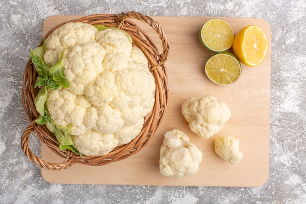 Top view of fresh cauliflower with lemon on white-light surface Free Photo