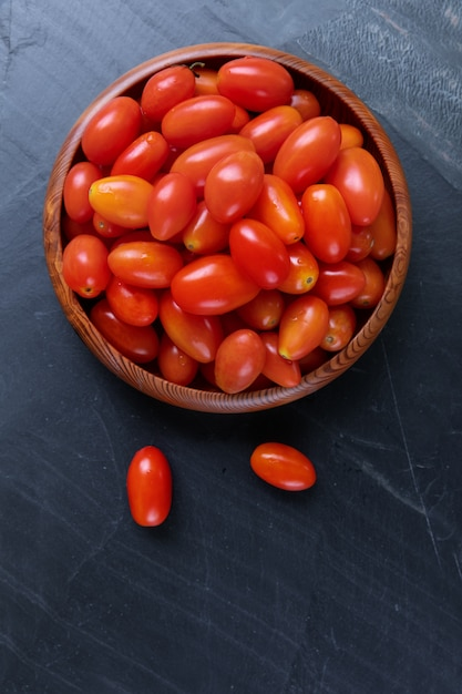 Top view of fresh cherry tomatoes on bowl wooden with white wall. Premium Photo