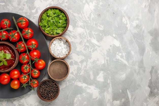 白い表面にさまざまな調味料を入れたプレート内の新鮮なチェリートマトの上面図 無料写真