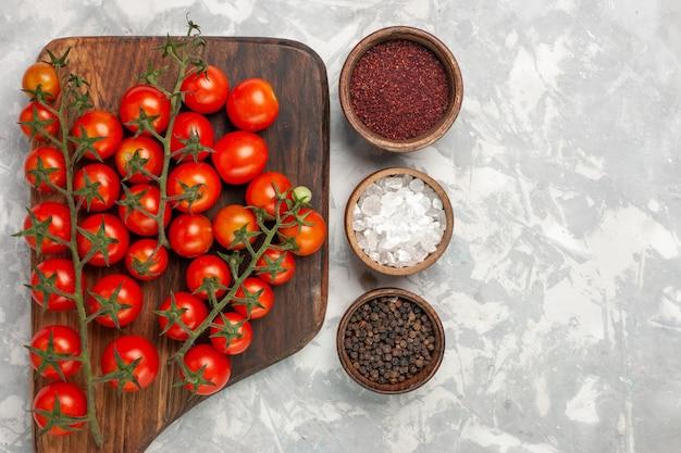 上面図新鮮なチェリートマトは、白い表面に調味料を加えた野菜全体を熟成させます 無料写真