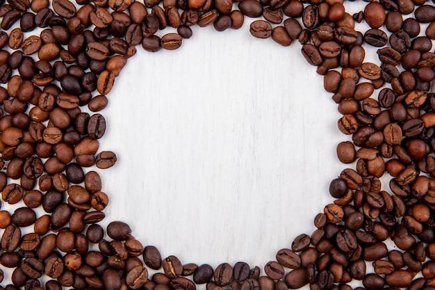 Vista dall'alto di chicchi di caffè freschi isolati su uno sfondo bianco con spazio di copia Foto Gratuite