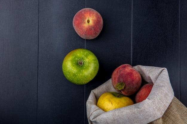 Vista dall'alto di frutta fresca e colorata come pesche e mele in sacchetti di iuta su fondo nero Foto Gratuite