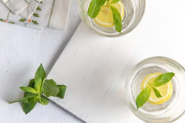 Vista dall'alto di limonata fresca fresca con limoni a fette all'interno di bicchieri su superficie bianco chiaro Foto Gratuite