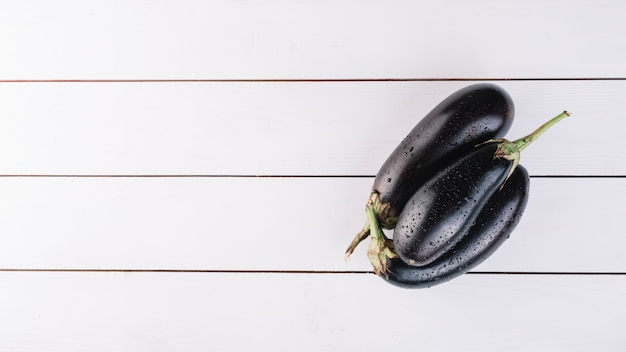 Top view of fresh eggplants on wooden plank Free Photo