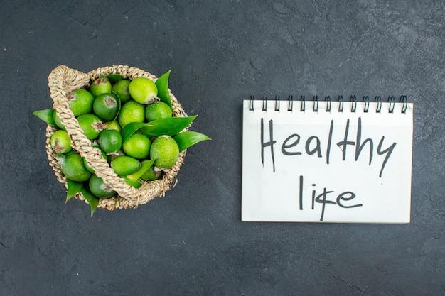 Вид сверху свежие фейхоа в корзине здорового образа жизни, написанные на ноутбуке на темной поверхности Бесплатные Фотографии