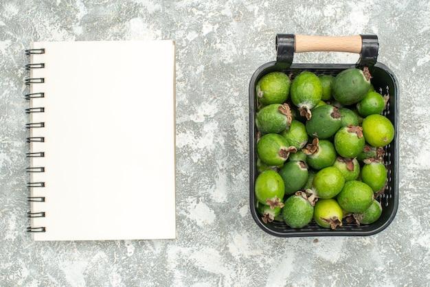 Вид сверху свежий фейхоас в корзине для ноутбука на серой поверхности Бесплатные Фотографии