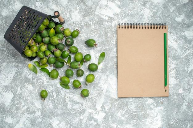 Вид сверху свежих фейхоа, разбросанных из тетради корзины и зеленого карандаша на серой поверхности Бесплатные Фотографии