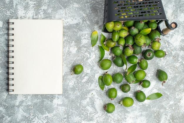 Вид сверху свежих фейхоа, разбросанных из записной книжки корзины на серой поверхности Бесплатные Фотографии