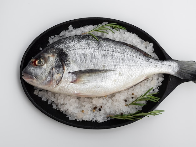 Top view fresh fish in pan with herbs Free Photo