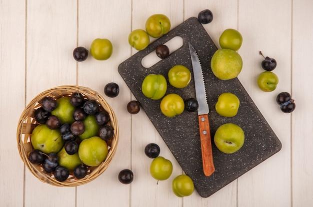 Vista dall'alto di prugne ciliegia verde fresco su un tagliere di cucina con coltello con prugne ciliegia e prugnole su un secchio su un fondo di legno bianco Foto Gratuite