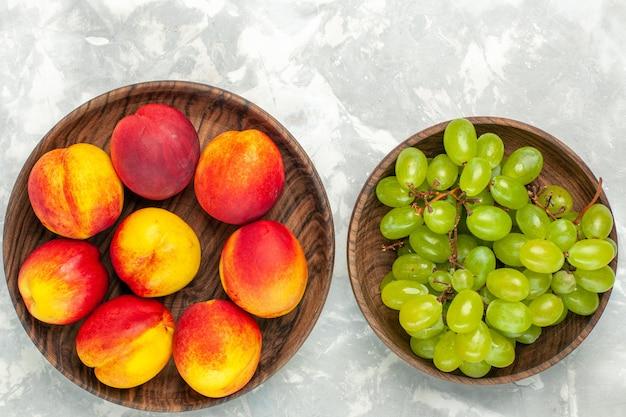 明るい白い机の上に桃とまろやかでおいしい新鮮な緑のブドウの上面図 無料写真