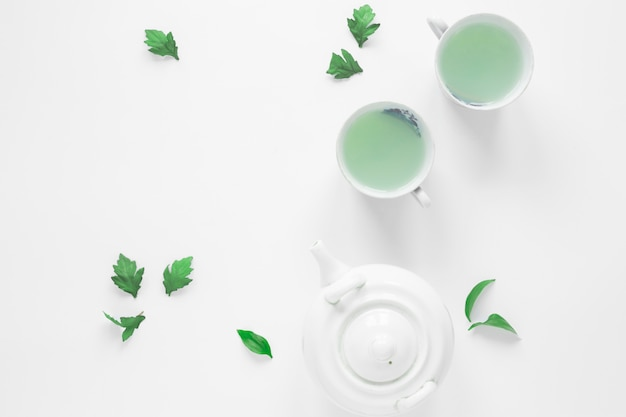 Top view of fresh green tea with tea leaves and teapot Free Photo