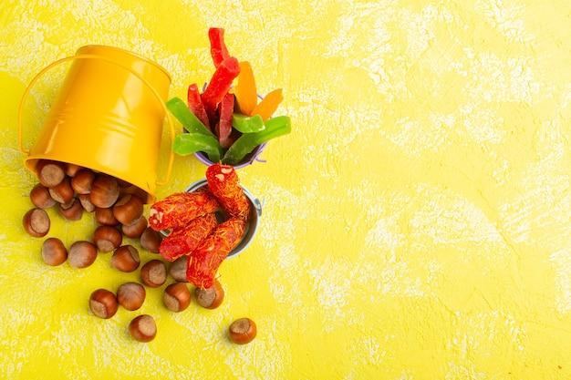 Vista dall'alto di nocciole fresche insieme a torrone e marmellate sulla superficie gialla Foto Gratuite