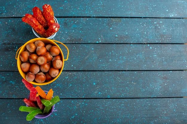 Vista dall'alto di nocciole fresche con torrone e marmellate sulla superficie blu Foto Gratuite