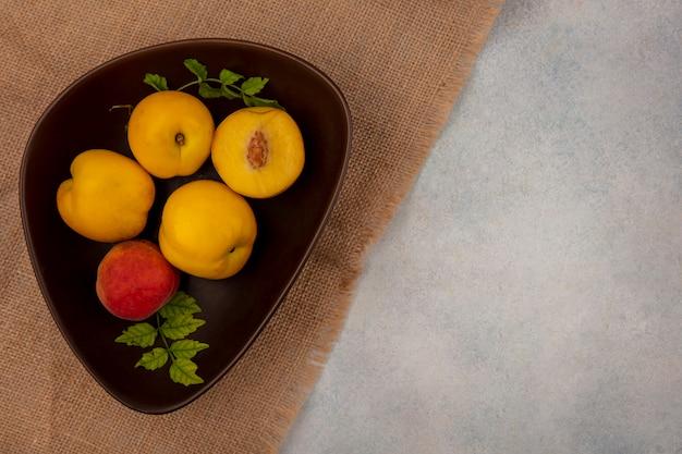 コピースペースと白い背景の上の袋布のボウルに新鮮なジューシーな黄色の桃の上面図 無料写真