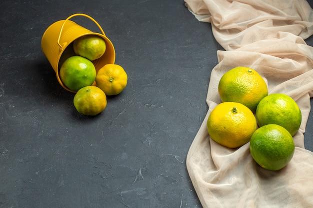 Limoni freschi di vista superiore sui limoni beige dello scialle di tule sparsi dal secchio sulla superficie scura con lo spazio della copia Foto Gratuite