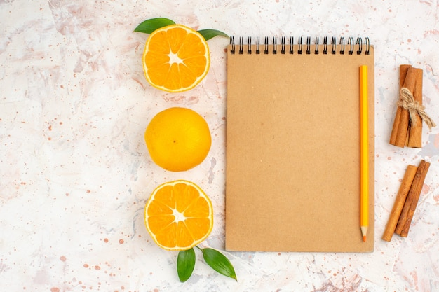 Top view fresh mandarines cut mandarines cinnamon sticks pencil on notebook on bright isolated surface with free space Free Photo