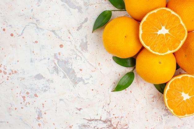 Vista dall'alto mandarini freschi arance sulla luminosa superficie isolata con copia spazio Foto Gratuite