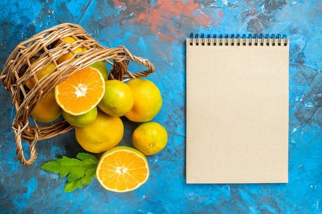 Вид сверху свежие мандарины на плетеной корзине блокнот на синей поверхности Бесплатные Фотографии