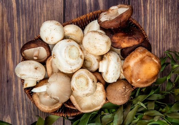 Top view of fresh mushrooms in a wicker basket on rustic wood Free Photo