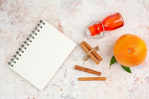 Vista dall'alto i bastoncini di cannella arancione freschi imbottigliano un taccuino sulla superficie luminosa Foto Gratuite