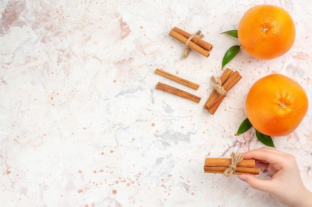 Vista dall'alto arance fresche bastoncini di cannella in mano femminile sulla superficie luminosa con spazio di copia Foto Gratuite