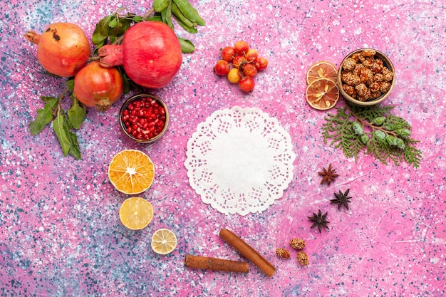 Top view fresh pomegranate with cinnamon on the pink surface Free Photo