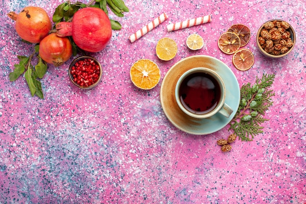 Top view fresh pomegranate with green leaves and cup of tea on the pink desk Free Photo
