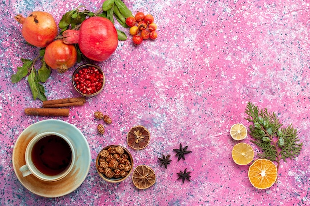 Top view fresh pomegranate with green leaves and cup of tea on pink surface Free Photo