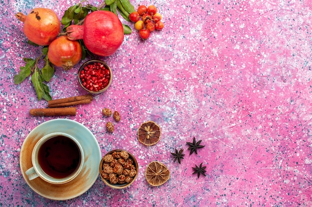 Top view fresh pomegranate with green leaves and cup of tea on the pink surface Free Photo