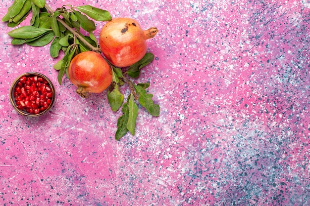 Top view fresh pomegranate with green leaves on pink desk Free Photo