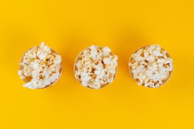 Una vista dall'alto popcorn fresco salato e gustoso su giallo, semi di mais spuntino Foto Gratuite