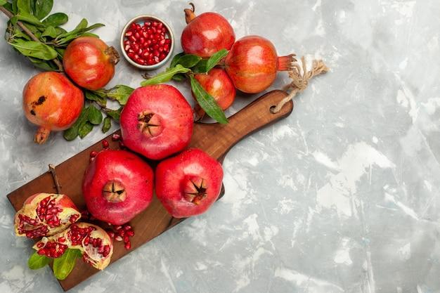 明るい白い机の上に新鮮な赤いザクロの酸っぱくてまろやかな果物の上面図 無料写真