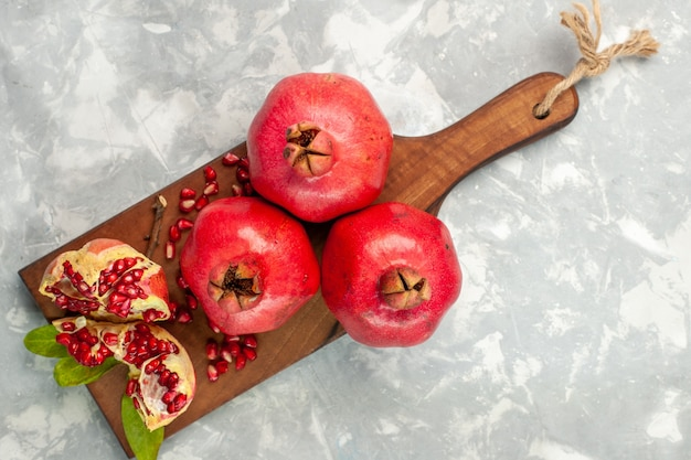 Top view fresh red pomegranates sour and mellow fruits on light-white desk Free Photo