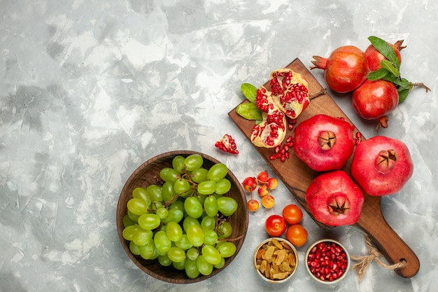 Top view fresh red pomegranates sour and mellow fruits with fresh green grapes on light-white desk Free Photo