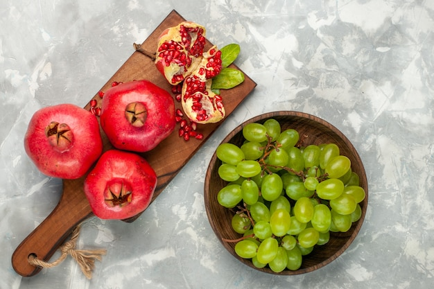 Top view fresh red pomegranates sour and mellow fruits with green grapes on light-white desk Free Photo