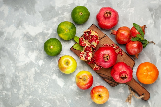 Top view fresh red pomegranates with tangerines and apples on the light-white desk Free Photo