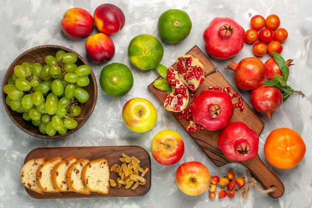 Top view fresh red pomegranates with tangerines cake and apples on the light-white desk Free Photo