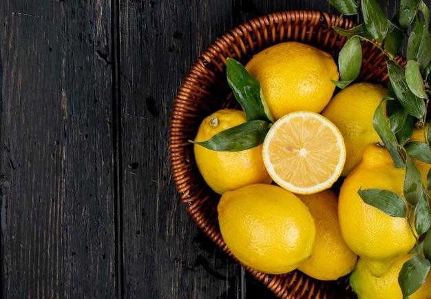 Vista superiore dei limoni maturi freschi in un cestino di vimini sul nero con lo spazio della copia Foto Gratuite