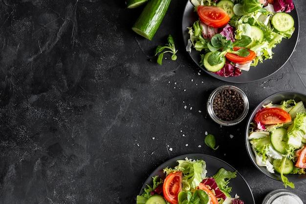 Вид сверху свежие салаты на темных тарелках с копией пространства Premium Фотографии