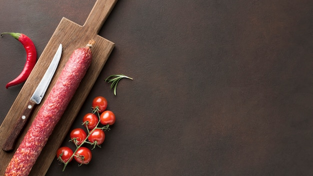 Top view fresh salami with cherry tomatoes Free Photo