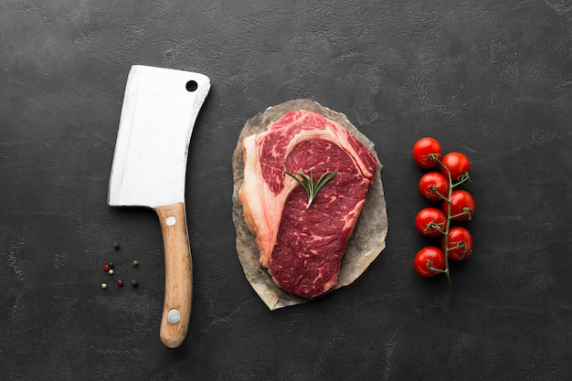 Вид сверху свежий стейк с ножом и помидорами черри Premium Фотографии