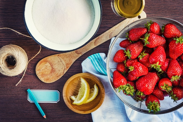 Top view of fresh strawberries, sugar and lemon zest. strawberry jam ingredients prepared to be cooked. Premium Photo