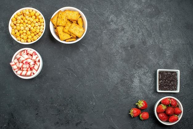 Fragole fresche vista dall'alto con diversi snack Foto Gratuite
