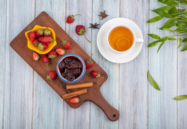Top view of fresh strawberries on a yellow bowl on a wooden kitchen board with a strawberry jam with cinnamon sticks with a cup of tea with leaves on a grey wooden background Free Photo