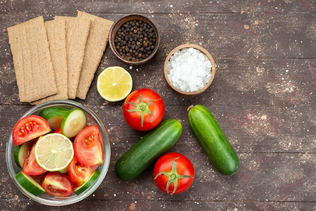 Vista dall'alto insalata di verdure fresche all'interno di vetro con limone insieme a patatine fresche di verdure intere su marrone Foto Gratuite
