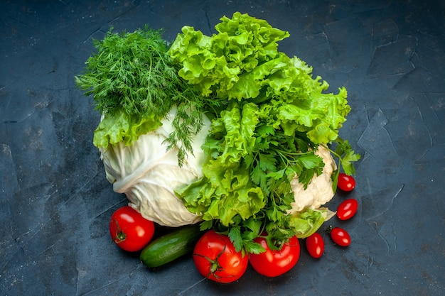 Top view fresh vegetables cabbage parsley bell peppers lettuce dill cauliflower tomatoes on dark surface Free Photo