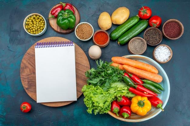 Vista dall'alto di verdure fresche con verdure e condimenti sulla verdura insalata di pranzo spuntino spuntino scrivania blu Foto Gratuite
